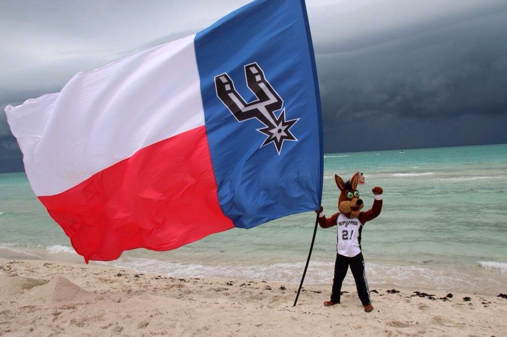 San Antonio Spurs Mascot holding a huge Texas Flag